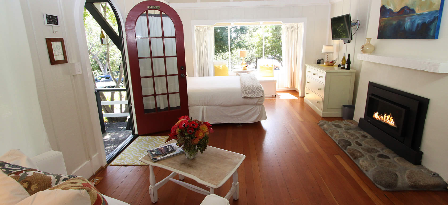 carmel bed and breakfast cottages - open door, bed, table and fireplace