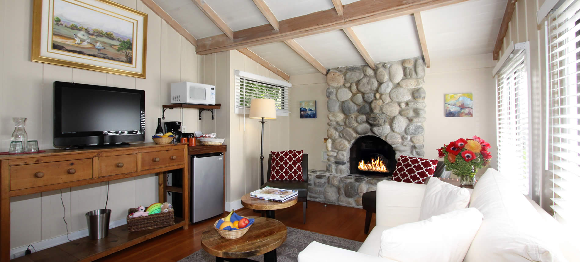 carmel boutique hotel guest room with couch, fireplace, tv and table with fruit