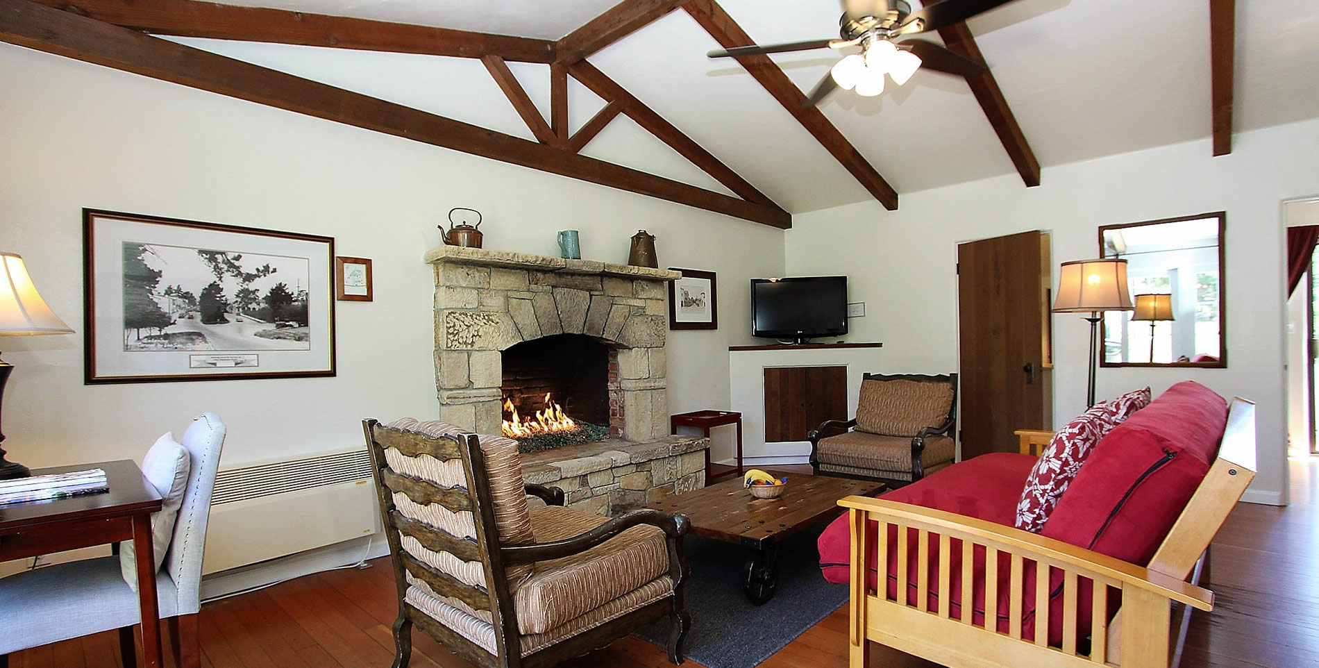 carmel vacation cottage living room with couch stone fireplace and chairs