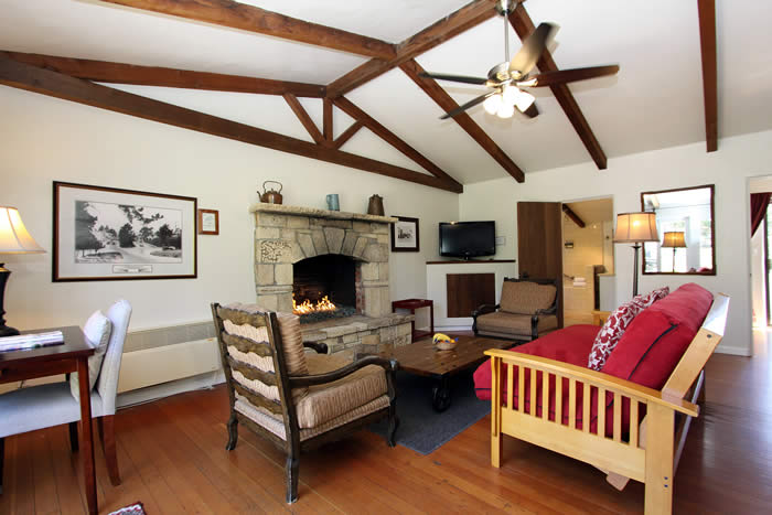 carmel lodging living room with fireplace, red couch, desk and chair