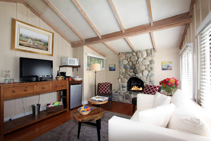 carmel lodging - room with couch, stone fireplace and TV