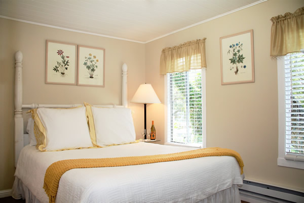guest room with bed, lamp and window