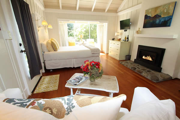 guest room with bed, fireplace, table and chairs